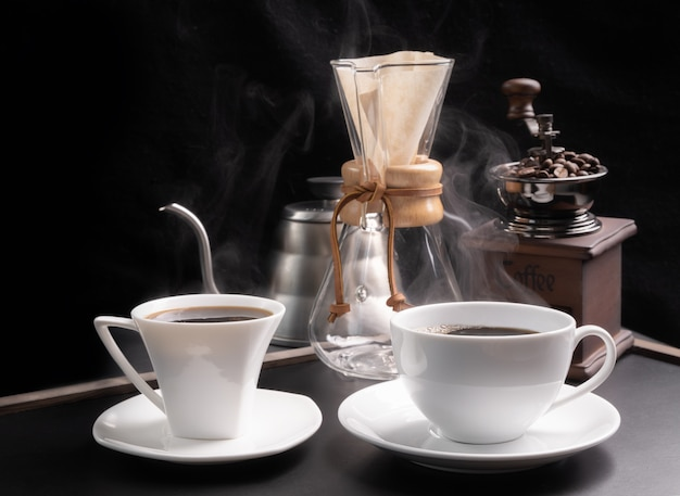 Steam coffee cups with coffee grinder,beans and kettle  on grunge wood table dark background