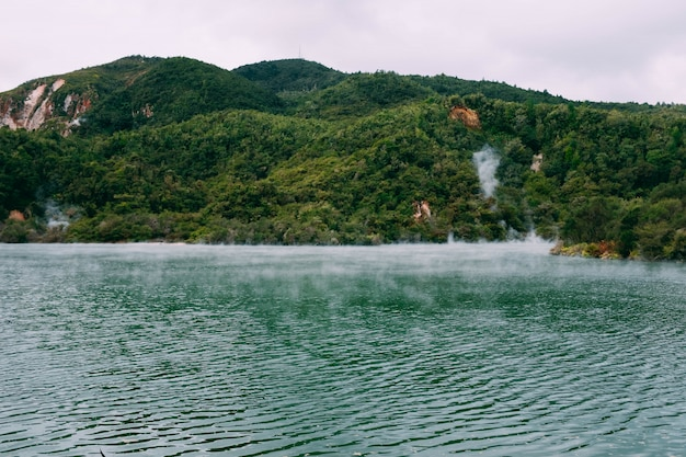 Steam coming out of a beautiful body of water surrounded by green mountains