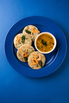 Ravaidliまたはidlyとして知られている蒸気調理されたセモリナケーキ。サンバーとココナッツのチャツネを添えて。セレクティブフォーカス