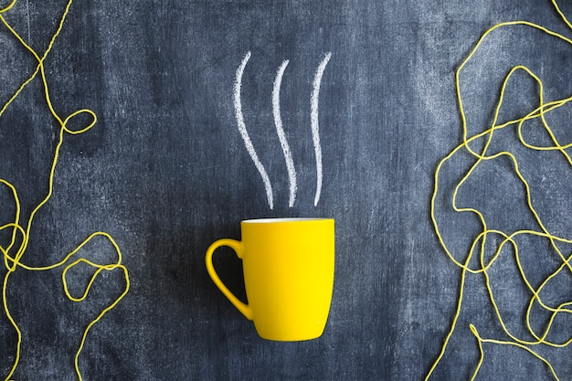 Steam drawn over the yellow mug with yellow wool thread on blackboard