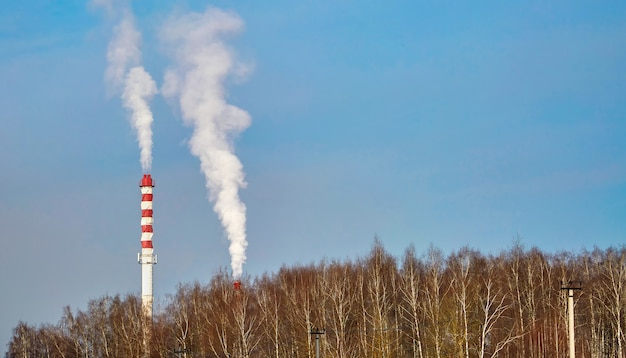 青い空を背景に建物を暖房するためのパイプからの蒸気。都市景観。
