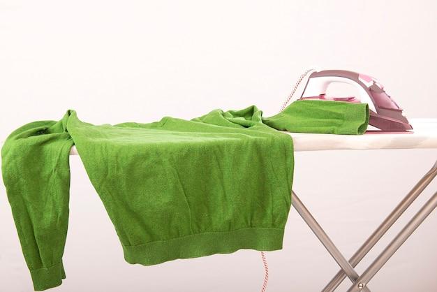 Паровой утюг и гладильная одежда зеленый свитер на гладильной доске изолированы.