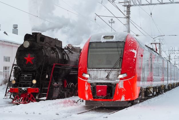 Зимой рядом на вокзале стоят паровоз и современный электропоезд.