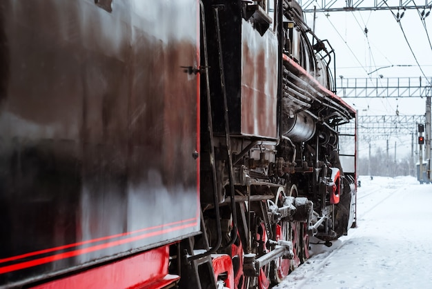Steam locomotive arrives at the railway junction in winter