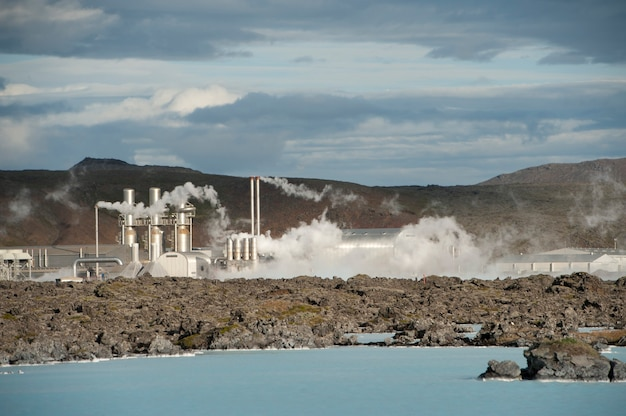 Steam rising from a geothermal power station above a rocky lake coastline