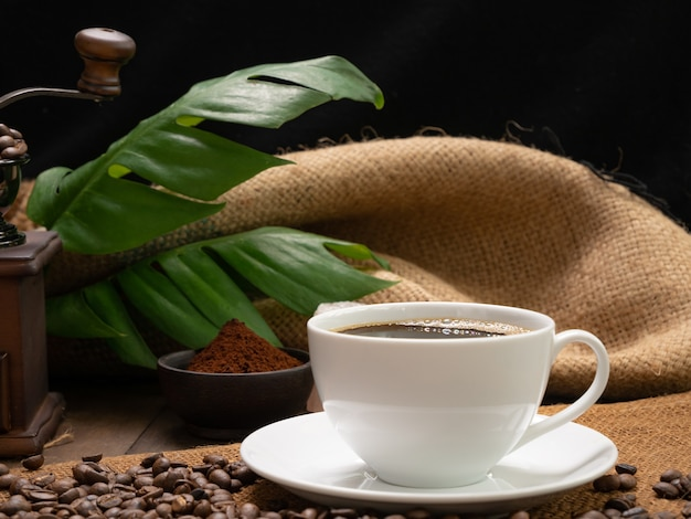 グランジウッドテーブルの表面にグラインダーローストビーンズコーヒーグラウンドグリーンの葉と黄麻布ヘシアンを添えたスチームホワイトコーヒーカップ