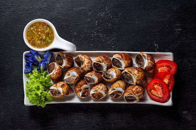 Steamed areola, spotted babylon with seafood dipping sauce on wooden table.