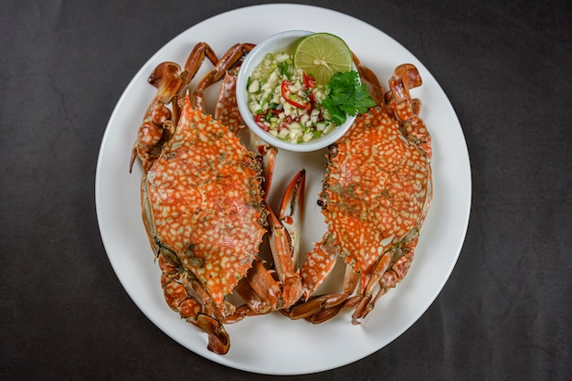 Steamed blue crab on white plate with spicy seafood sauce