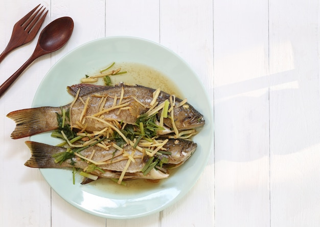 Steamed blue point grouper fish with soy sauce in white dish.