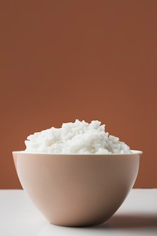 Steamed boiled rice in ceramic bowl against brown background