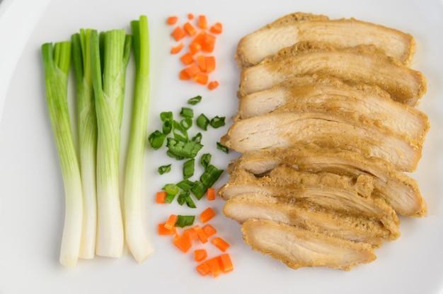 봄 양파와 다진 당근 흰 접시에 찐 닭 가슴살