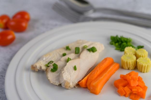 Petto di pollo al vapore su un piatto bianco con cipollotti, mais e carote tritate.