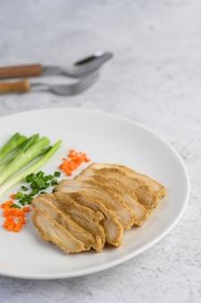 Petto di pollo al vapore su un piatto bianco con cipollotti e carote tritate