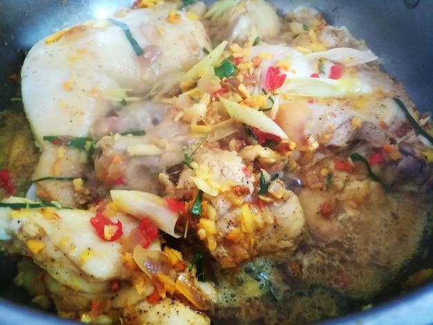 タイのハーブと鍋で蒸し鶏をクローズアップ