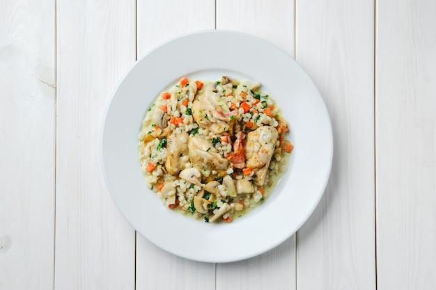 Куриное мясо на пару с рисом, грибами и морковью с соусом на белом деревянном столе