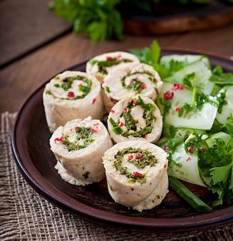 Куриные рулетики на пару с зеленью и салатом из свежих овощей на коричневой тарелке