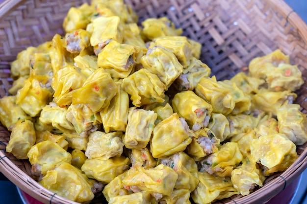 タイの屋台の食べ物市場で竹の蒸し点心、クローズアップ。点心は、スナックまたはメインコースとして提供される、さまざまな詰め物を含む小さな蒸しまたは揚げたおいしい餃子の中華料理です