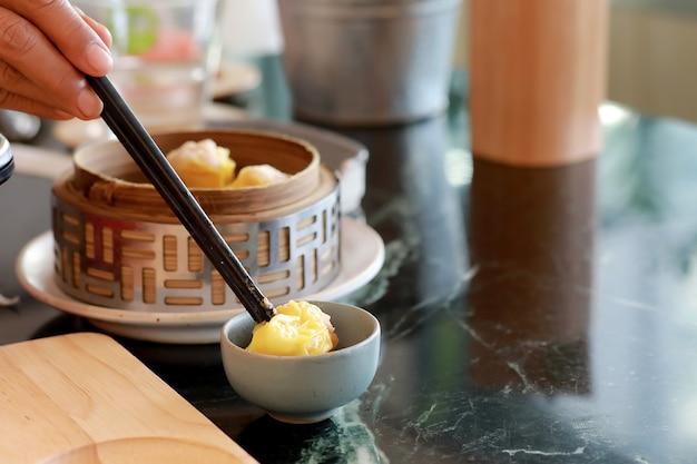Steamed dumpling shrimp dim sum in bamboo steamer with hand and chopsticks.