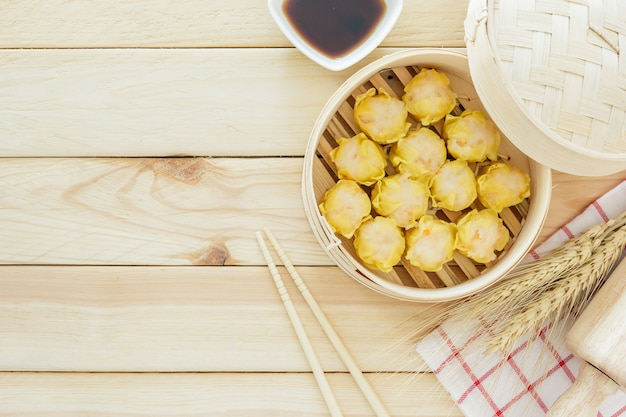 Steamed dumplings (chinese dim sum) in bamboo basket, serve with chopsticks on wooden tabl
