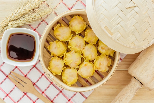 Steamed dumplings (chinese dim sum) in bamboo basket on wooden table background