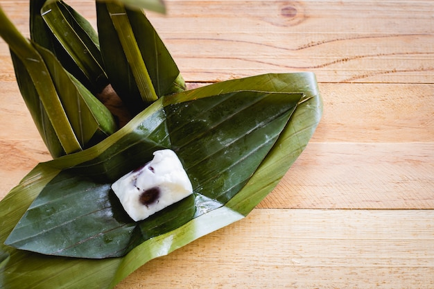 Steamed flour custard with sweet coconut filling on wooden background for thai dessert concept