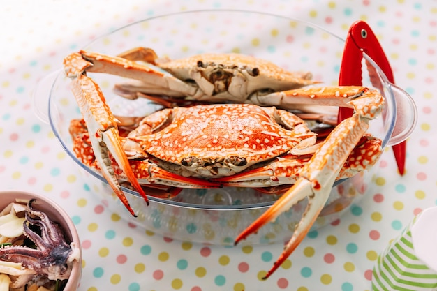 Steamed fresh flower crabs in glass bowl with red crab cracker.