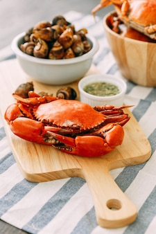 Steamed giant mud crab on wooden chopping board served with thai spicy seafood sauce and grilled laevistrombus canarium in shell