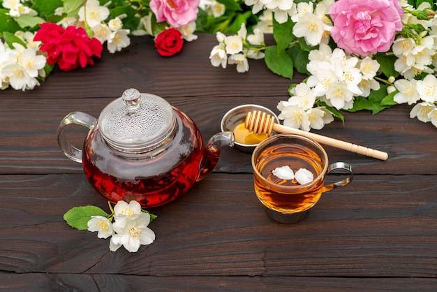 Чайник из вареного стекла, элегантная чашка с чаем и лепестками меда на деревянном столе