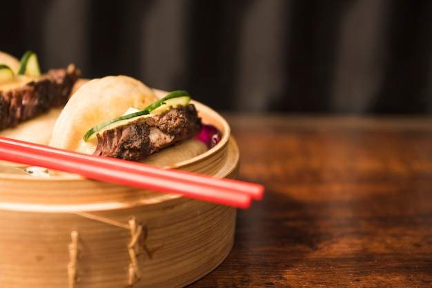 Steamed gua bao in the steamers with red chopsticks over the wooden table