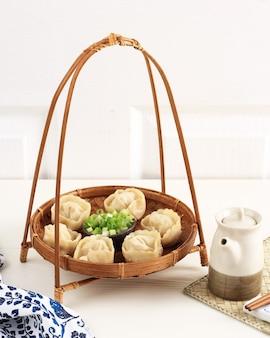 찐만두 만두, 한국 전통 딤섬 길거리 음식. 다진 파와 간장 소스를 곁들인 대나무 접시에 제공