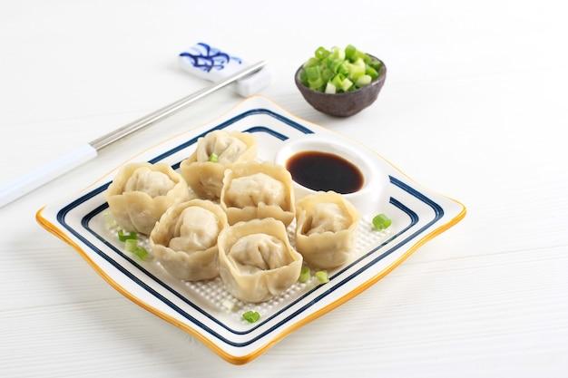 찐만두 만두, 한국 전통 딤섬 길거리 음식. 다진 파와 간장 소스를 곁들인 사각 접시에 제공