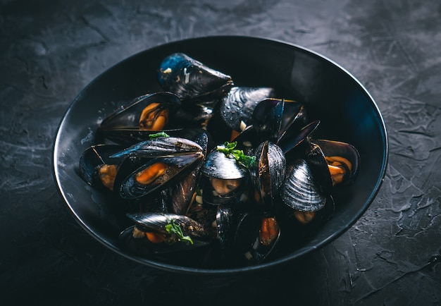 Steamed mussels in a black bowl on a dark table