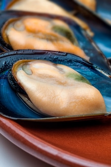 Steamed mussels close-up. with shell on clay plate.