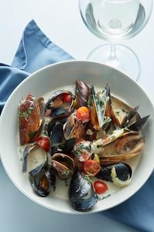 テーブルの上の白ワインソースで蒸したムール貝