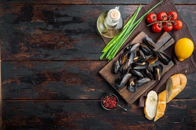 白ワインセットの蒸しムール貝、木製のまな板、古い暗い木製のテーブル、上面図フラットレイ