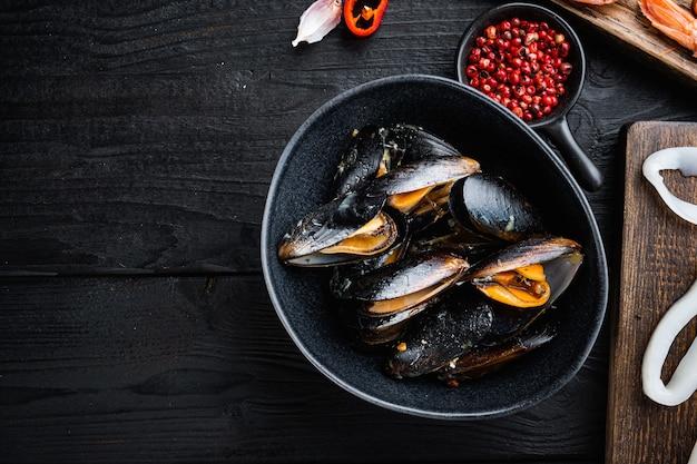 黒い木のテーブルの上に蒸したムール貝、平らな横たわり