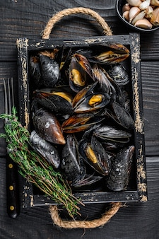 Steamed mussels in shells in a wooden tray with herbs