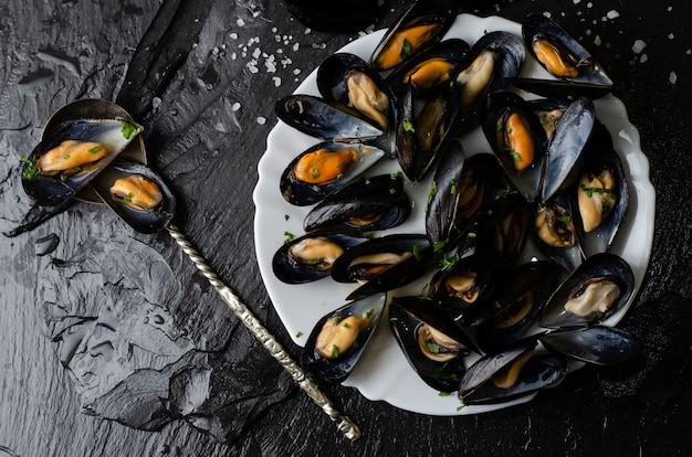 Steamed mussels with parsley on dark