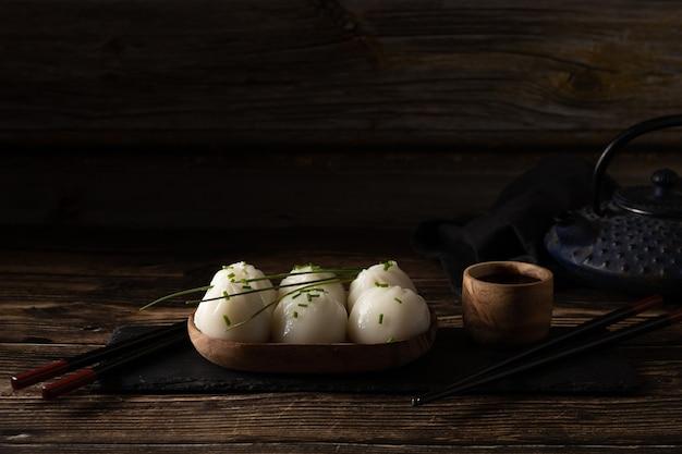 茶色の木製テーブルのスレート石に蒸した豚肉とエビの点心