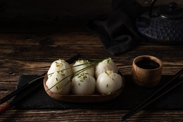 Димсам из свинины и креветок на сланце на деревянном столе в азиатском ресторане