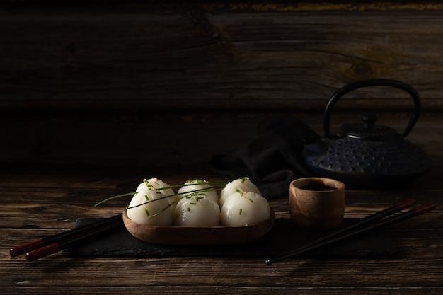 Димсам из свинины и креветок на сланце на деревянном столе