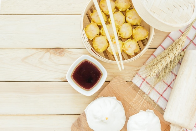 Steamed pork buns (chinese dim sum) in bamboo basket, serve with chopsticks on wooden tabl