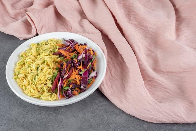 Тушеный рис и овощной салат на белой тарелке. фото высокого качества