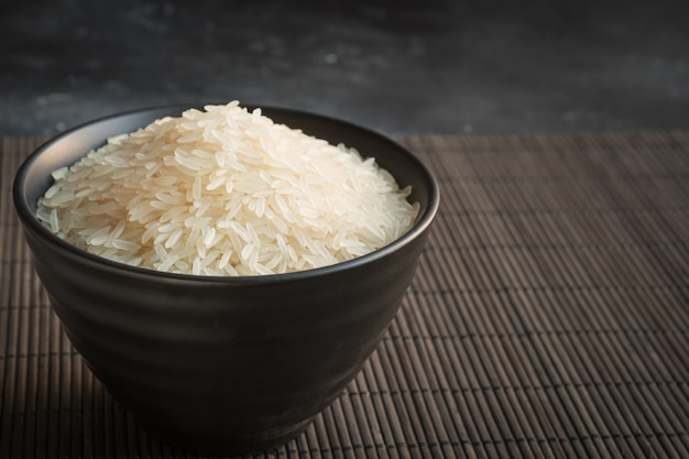 Steamed rice in bowl on black background. copy space.