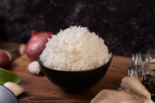 Steamed rice in a bowl with garlic and red onion on a wooden cutting board