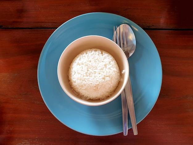 나무 테이블에 숟가락과 포크가 있는 그릇에 찐 쌀