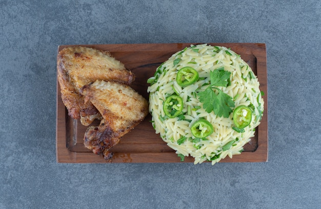 木の板に鶏肉の部分が入ったご飯。