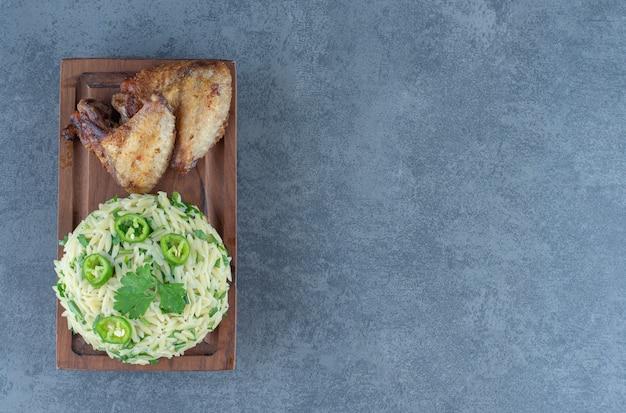 Riso al vapore con parti di pollo su tavola di legno.