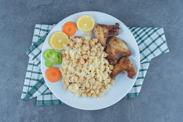Вареный рис с нутом и куриными крылышками на белой тарелке.