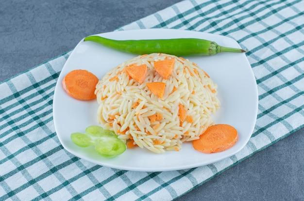 Вареный рис с нарезанной морковью на белой тарелке.